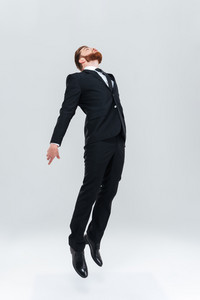 Full length business man in black suit flying or jumping in stuio. Isolated gray background