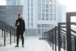 Full length business man in glasses and warm clothes holding coffee in hands and standing on the stairs as well as looking away