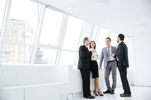 Full length Business team stand and talk near the window in conference room