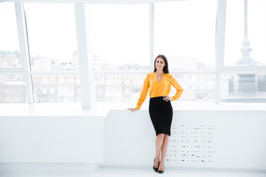Full length Business woman in orange shirt standing near the window in office and looking at camera