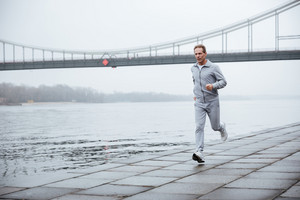 Full length elderly Man in gray sportswear running near the water. Side view