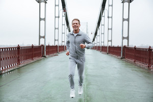 Full length Elderly Man in gray sportswear running on bridge