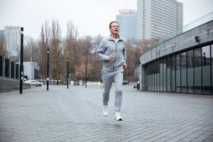 Full length Elderly Man in gray sportswear running on the street