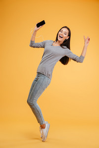 Full length girl listening to music at phone in studio. with eyes closed. isolated orange background