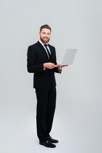 Full length handsome bearded business man in black suit holding laptop and looking at camera. Isolated gray background