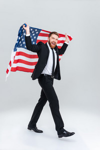 Full length happy bearded business man in black suit holding USA flag from the back. Side view. Isolated gray background