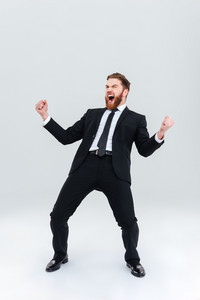 Full length happy bearded business man in black suit. Isolated gray background
