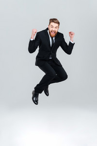 Full length happy business man in black suit jumping in studio. So happy man. Isolated gray background