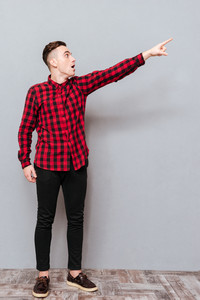 Full length Hipster in red shirt pointing and looking away. Isolated gray background