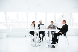 Full length image of Business people sitting by the table on conference in office