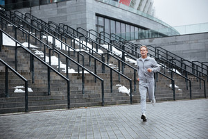 Full length Man in gray sportswear running near the stairs.