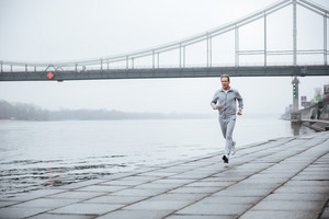 Full length Man in gray sportswear running near the water.