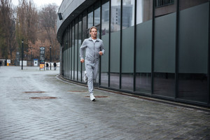 Full length Man in gray sportswear running on the street