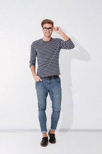 Full length man in striped sweater and glasses posing with arm in pocket and holding his eyeglasses