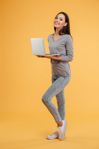 Full length model with laptop in studio. side view. isolated orange background