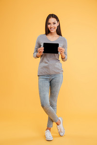 Full length model with tablet in studio. isolated orange background