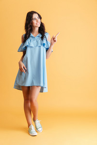 Full length of a cheerful pretty woman in blue dress pointing finger away over orange background