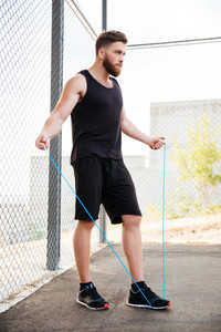 Full length of a concentrated fitness man doing cardio exercises with skipping rope outdoors