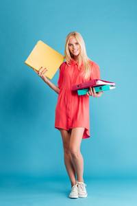 Full length of a happy blonde woman holding folders and looking at camera over blue background