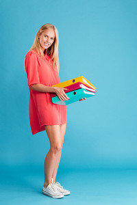 Full length of a smiling pretty young woman holding folders with documents isolated on the blue background