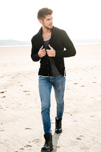 Full length of a young casual man walking across the beach in the morning sun