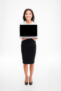 Full length of a young smiling asian businesswoman showing laptop with blank screen isolated on the white background