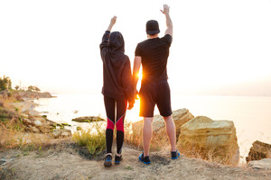Full length of a young sports couple standing together at the sunset and waving hands