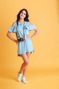 Full length of a young woman photographer in dress standing with retro camera isolated on a orange background