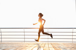 Full length of attractive young sportswoman running on pier at sunrise