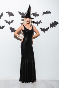 Full length of attractive young woman in black witch costume with hat standing over white background
