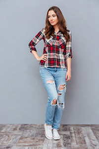 Full length of attractive young woman in checkered shirt and jeans standing