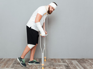 Full length of bandaged young man walking with crutches over white background