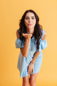 Full length of beautiful positive young woman in dress sending a kiss isolated on a orange background
