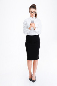 Full length of beautiful young business woman in glasses standing and using smartphone over white background