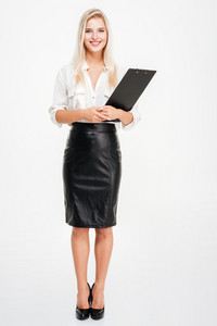 Full length of beautiful young businesswoman standing and holding clipboard over white background