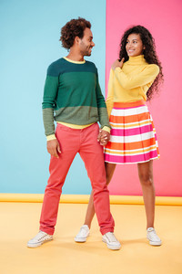 Full length of cheerful african young couple standing and holding hands over colorful background