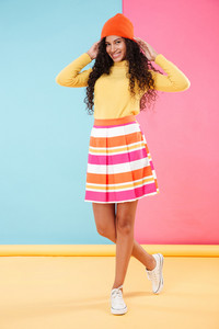 Full length of cheerful attractive african young woman standing and smiling over colorful background
