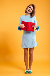 Full length of cheerful beautiful young woman standing and holding red book over yellow background