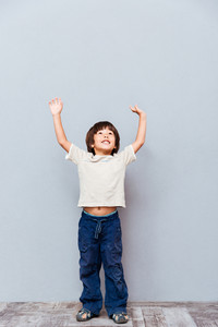 Full length of cheerful little boy standing with raised hands over gray background