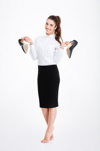 Full length of cheerful pretty young businesswoman standing and holding high heels shoes over white background