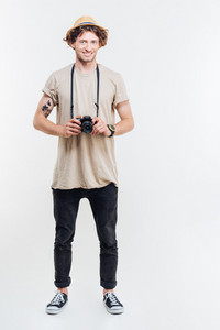 Full length of cheerful young man standing and holding old vintage photo camera over white background
