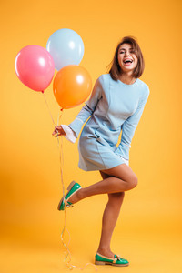 Full length of cheerful young woman with balloons standing and laughing over yellow background