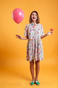 Full length of cheerful young woman with pink balloon and lollipop standing over yellow background