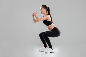 Full length of concentrated young woman athlete doing squats over gray background