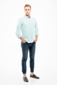 Full length of confident handsome young man standing with hands in pockets over white background