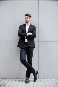 Full length of confident young businessman standing with arms crossed