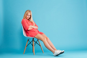 Full length of disappointed upset blonde woman in red dress sitting on chair isolated on the blue background