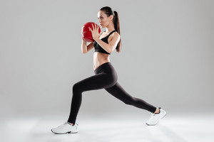 Full length of focused beautiful young sportswoman doing exercises with medicine ball over gray background