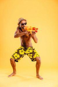Full length of funny young afro american man in swimwear shooting with water gun over orange background