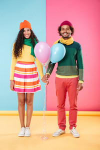 Full length of happy african american young couple in hats and scarves holding balloons